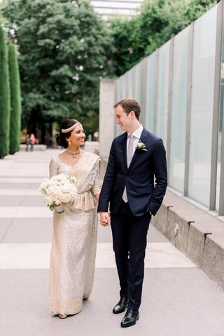 intercultural-bride-and-groom-south-asian-bride-in-gold-and-ivory-sari-white-groom-in-navy-suit
