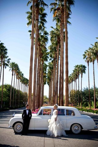 newlyweds-next-to-antique-automobile-and-palm-trees