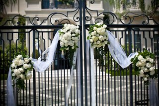 wrought-iron-gate-decorated-with-white-flowers