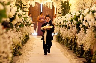 little-boy-walking-down-floral-embellished-aisle
