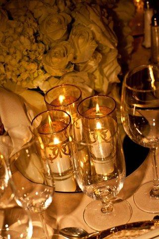 white-votive-candles-in-gilt-pillar-vases