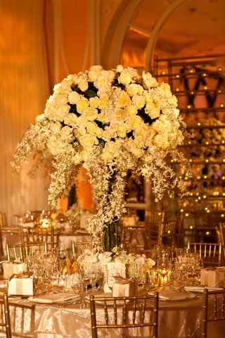 gold-chairs-around-table-topped-with-large-arrangement