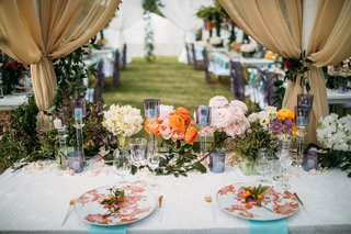 wedding reception sweetheart table under gold drapery orange pink flowers purple candles flower
