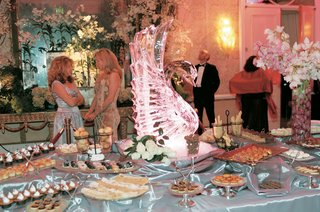 wedding-dessert-table-decorated-with-a-swan-ice-sculpture-and-pink-orchid-bouquet