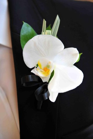 single-white-flower-and-palm-fronds-on-lapel