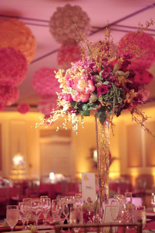 wedding-reception-table-with-a-centerpiece-of-pink-orange-and-yellow-flowers