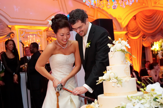 bride-and-groom-cut-white-wedding-cake-with-large-sword