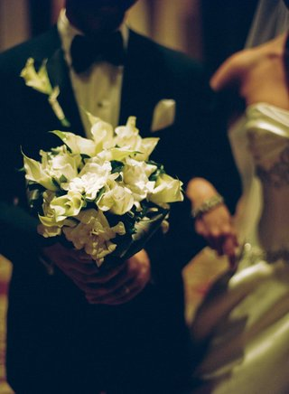groom-carrying-his-brides-ivory-bouquet