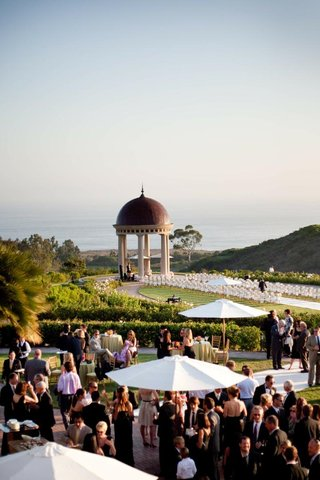guests-mingle-at-cocktail-hour-with-ceremony-backdrop