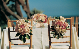 table-with-floral-centerpiece-and-flowers-on-chair