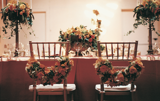 floral-garlands-on-backs-of-bride-and-groom-dinner-chairs