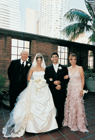 bride-and-groom-with-a-man-in-a-tuxedo-and-a-woman-in-a-long-pink-dress