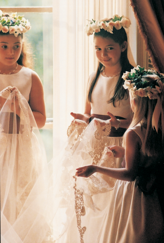 three-flower-girls-wearing-rose-crowns-hold-the-brides-veil