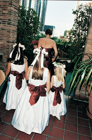 flower-girls-walk-down-the-aisle-in-white-dresses-and-red-sashes