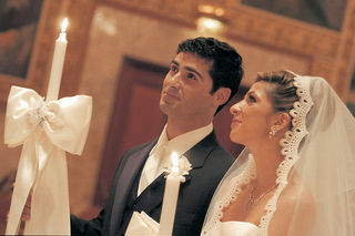 bride-and-groom-hold-candles-during-greek-wedding-ceremony