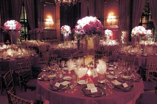 round-reception-tables-decorated-with-red-lavender-and-fuchsia-roses-in-a-tall-glass-vase