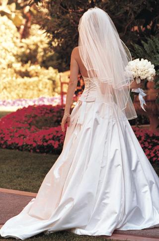 bride-in-garden-holding-bouquet-in-gown
