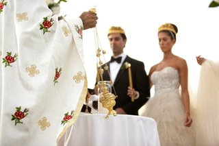 bride-and-groom-wearing-gold-crowns-at-altar