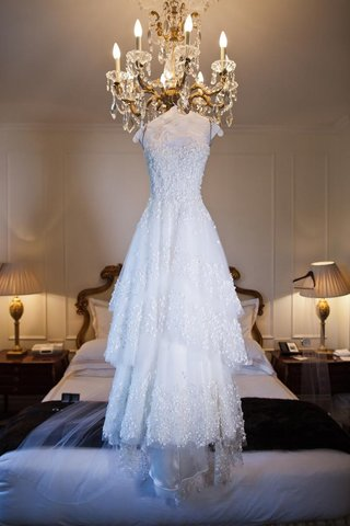 monique-lhuillier-tiered-skirt-wedding-dress-hanging-from-chandelier