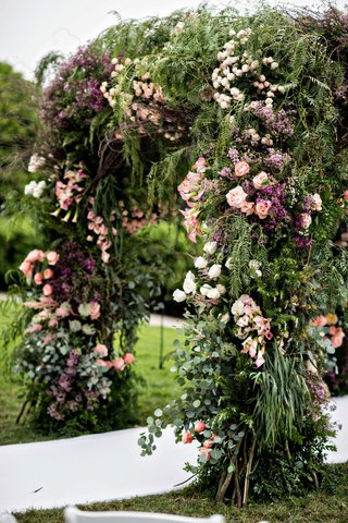 wedding ceremony flowers pink purple greenery lush archway for outdoor ceremony