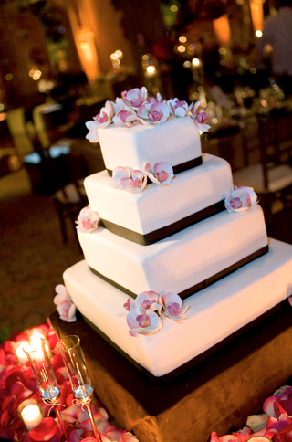 square-white-cake-with-brown-trim-around-tiers-and-pink-flowers-on-top-and-sides
