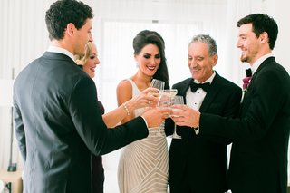 bride-in-naeem-khan-wedding-dress-with-father-and-mother-of-bride-and-bridesmen-toasting-champagne