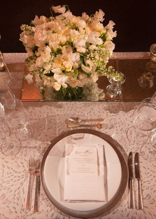 white-table-linens-and-china-plateware-with-low-white-floral-arrangements-on-mirror-stand