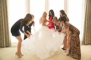 women-help-bride-with-ruffles-on-wedding-dress