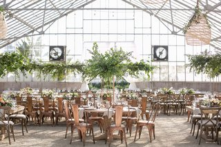 wedding-reception-greenhouse-venue-tall-greenery-trees-industrial-copper-chairs-high-low-centerpiece