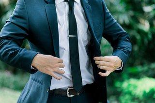 groom-in-dark-suit-putting-on-jacket-skinny-tie-tie-clip-outdoor-wedding