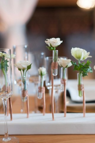 miniature-white-and-green-floral-arrangements-in-clear-tubes-help-up-by-copper-wire