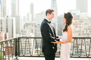 groom-and-bride-holding-each-others-arms-during-first-look-on-balcony-in-chicago-skyline
