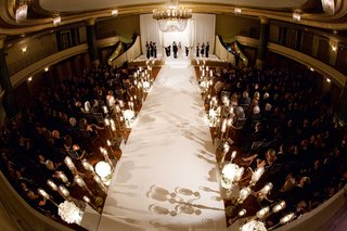 long-white-aisle-runner-lined-with-candelabra-candles-chandelier-oval-drapery-chuppah-and-guests
