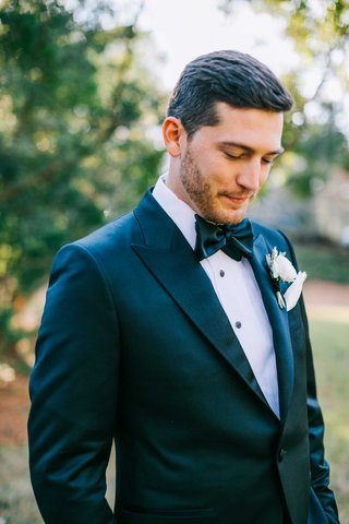 dapper-groom-with-bow-tie-and-white-boutonniere