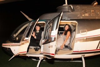 groom-and-bride-in-monique-lhuillier-wedding-dress-inside-helicopter-for-wedding-reception-exit