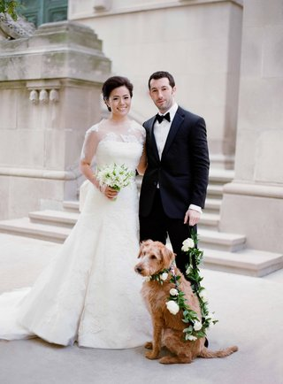 bride-in-vera-wang-wedding-dress-holding-bouquet-lily-of-the-valley-groom-tuxedo-dog-with-leash