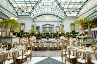 wedding-reception-at-harold-washington-library-in-chicago-greenery-gold-chairs-skylight-tall-ceiling