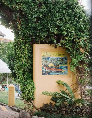 wedding-rehearsal-dinner-mexico-location-venue-with-tile-sign-grass-lawn-hedge-wall
