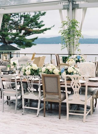 antique-seating-chairs-around-wood-tables-without-linens-open-side-tent-wedding-reception-by-lake