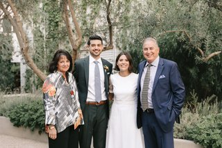 wedding-photo-of-groom-and-bride-with-father-of-groom-in-navy-suit-and-mother-of-groom-dress-shirt
