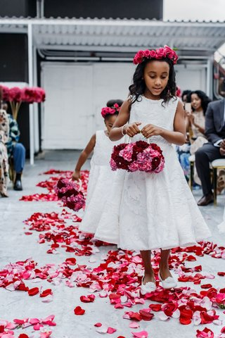 two-flower-girls-in-white-dresses-walking-down-petal-strewn-aisle-with-flower-basket-flower-crown