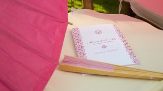 outdoor-wedding-ceremony-with-pink-parasol-and-fan-on-chair