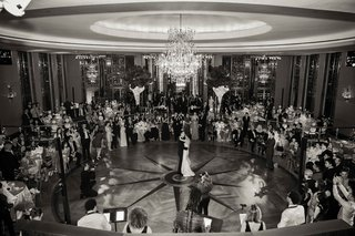 black-and-white-photo-of-bride-and-groom-first-dance-in-center-of-dance-floor-guests-watching