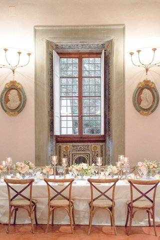 wedding-reception-villa-venue-vineyard-chairs-white-table-low-centerpiece-window-sconce-five-arm