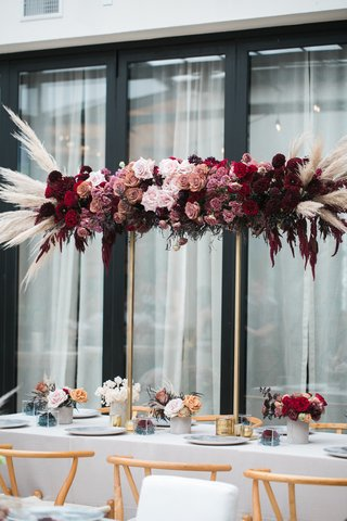 burgundy-red-mauve-roses-with-pampas-grass-on-gold-stand