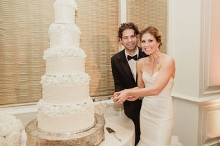 bride-in-strapless-wedding-dress-sweetheart-neckline-groom-in-suit-with-bow-tie-cutting-into-cake