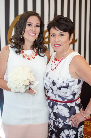 bride-in-a-white-dress-with-coral-necklace-white-bouquet-and-mother-in-black-and-white-floral-dress