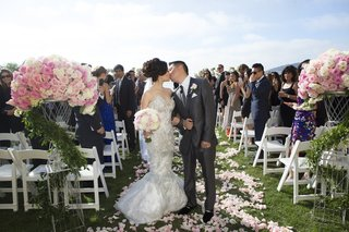 bride-and-groom-kiss-at-end-of-flower-petal-outdoor-aisle