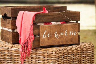 wooden-crate-filled-with-blankets-pashminas-wedding-favor-outdoor-be-warm-wood-calligraphy-signage