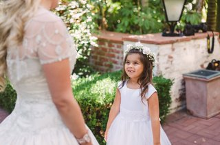 flower-girl-in-cap-sleeve-flower-girl-dress-and-flower-crown-looks-up-at-bride-missing-tooth